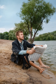 Geschäftsmann im zerrissenen anzug, der zeitung am strand auf verlorener insel liest. geschäftsrisiko, zusammenbruch oder insolvenzkonzept