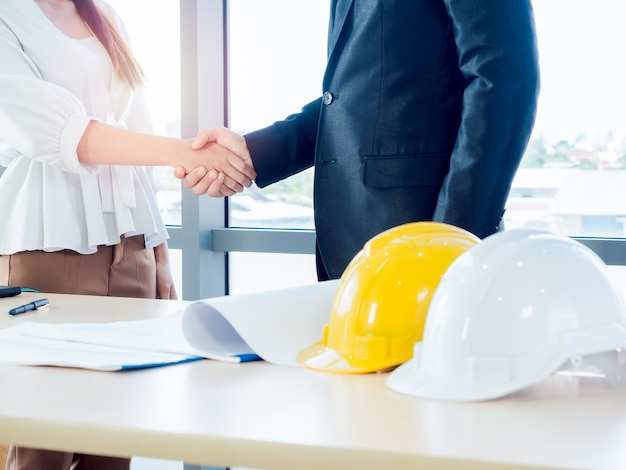 Geschäftsmann in anzug, ingenieurwesen oder architekt und frau, die hände auf blaupause und gelbem und weißem sicherheits-schutzhelm auf schreibtisch auf glasfenster schütteln.