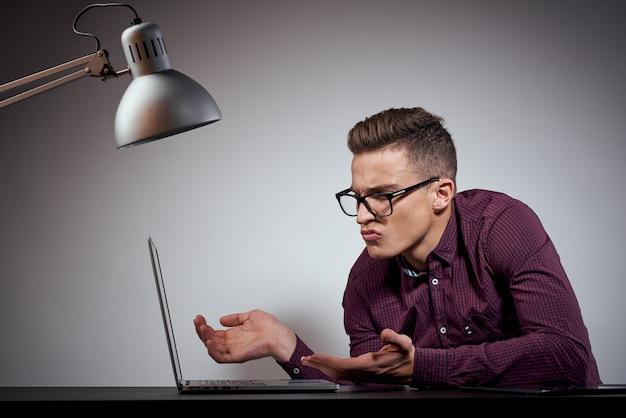 Geschäftsmann in brille und hemd sitzt an einem tisch mit offenen laptops