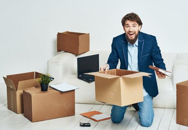 Geschäftsmann in den büroboxen mit sachen, die arbeit bewegen