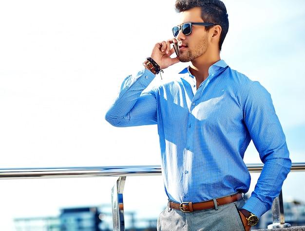 Geschäftsmann in der formalen kleidung und in der sonnenbrille unter verwendung seines telefons