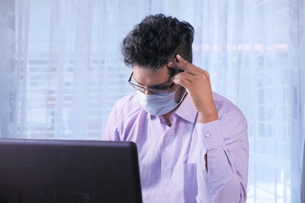 Geschäftsmann in der gesichtsmaske, die am laptop arbeitet