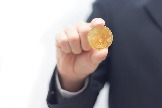 Geschäftsmann in der klage, die ein goldenes bitcoin anhält
