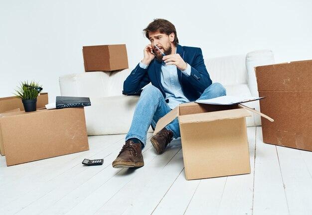 Geschäftsmann in der nähe von kisten mit dingen, die auspacken, die zu einem neuen standortbüro bewegen.