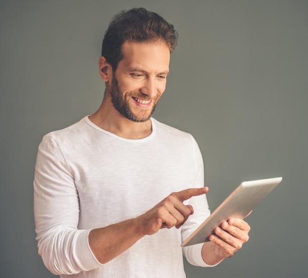 Geschäftsmann in der zufälligen kleidung benutzt eine digitale tablette