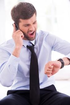 Geschäftsmann in eile. wütender junger mann in hemd und krawatte, der die zeit überprüft und auf dem handy spricht, während er auf dem bett sitzt