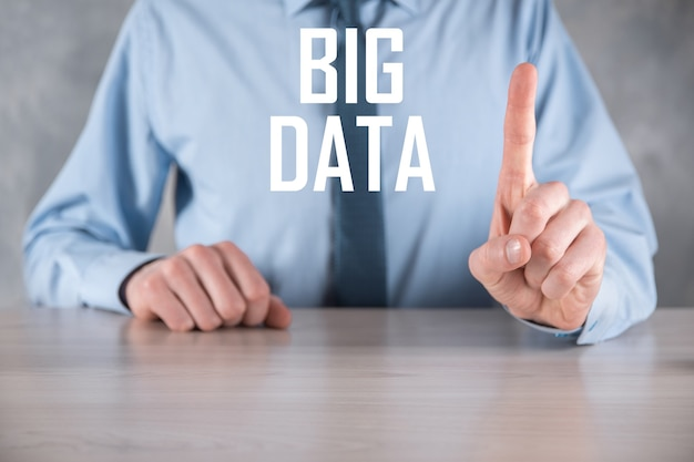 Geschäftsmann in einem anzug an einer dunklen wand hält die aufschrift big data. storage network online server concept.social network oder business analytics darstellung.