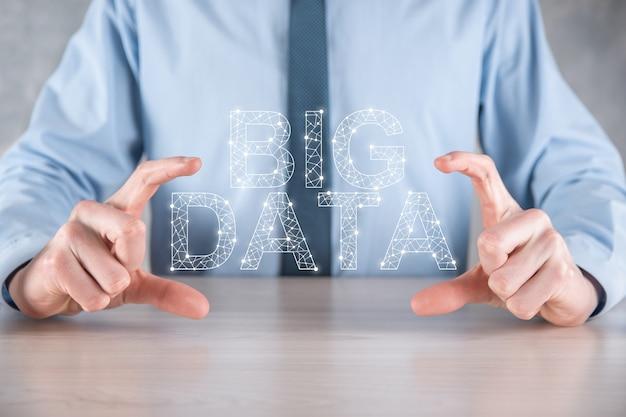 Geschäftsmann in einem anzug an einer dunklen wand hält die inschrift big data. storage network online server concept.soziales netzwerk oder business analytics-darstellung.