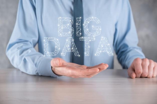 Geschäftsmann in einem anzug an einer hellen wand hält die aufschrift big data. storage network online server concept.soziales netzwerk oder business analytics-darstellung.