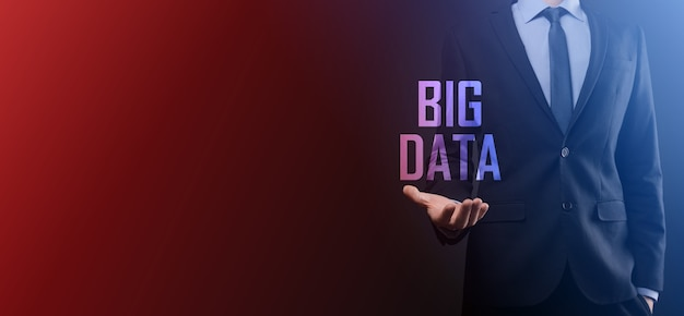 Geschäftsmann in einem anzug auf dunklem hintergrund hält die aufschrift big data. storage network online server concept. social network oder business analytics darstellung