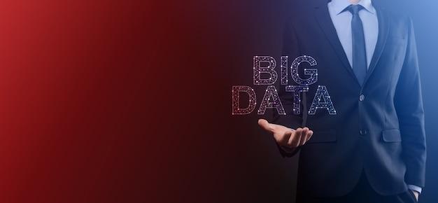 Geschäftsmann in einem anzug auf dunklem hintergrund hält die aufschrift big data. storage network online server concept.social network oder business analytics darstellung.