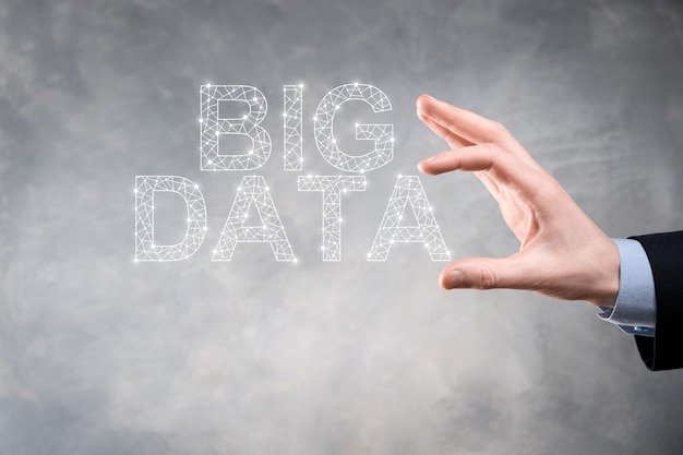 Geschäftsmann in einem anzug auf einem dunklen hintergrund hält die inschrift big data. storage network online server concept.soziales netzwerk oder business analytics-darstellung.