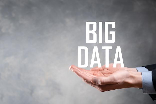 Geschäftsmann in einem anzug auf einer dunklen oberfläche hält die inschrift big data
