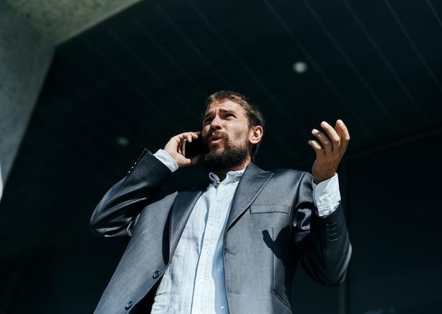 Geschäftsmann in einem anzug, der am telefon im freien business manager executive spricht