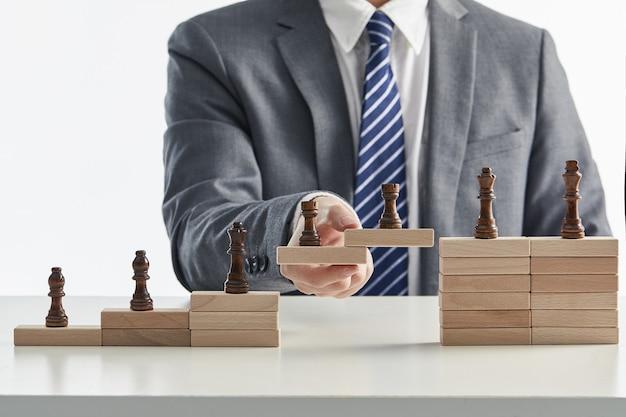 Geschäftsmann in einem anzug, der die lücke zwischen der unternehmenshierarchie überbrückt