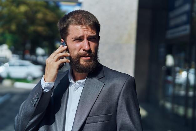 Geschäftsmann in einem anzug, der draußen am telefon spricht