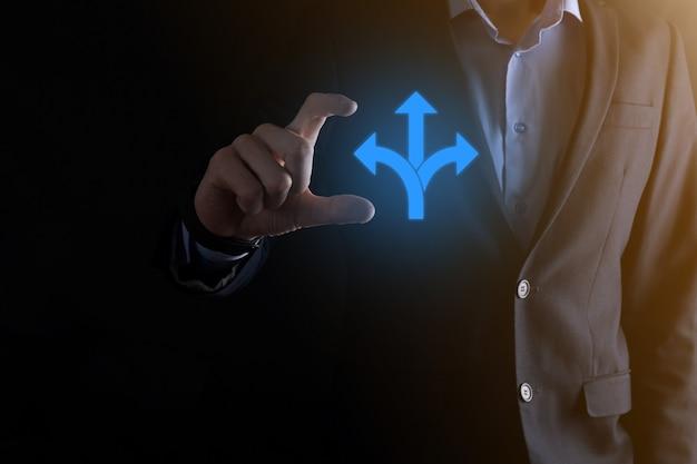 Geschäftsmann in einem anzug hält ein schild mit drei richtungen. im zweifelsfall zwischen drei verschiedenen möglichkeiten wählen zu müssen, die durch pfeile angezeigt werden, die in die entgegengesetzte richtung weisen. drei möglichkeiten zur auswahl