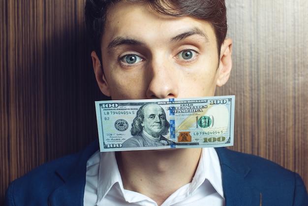 Geschäftsmann in einem anzug mit dollar auf dem geschlossenen mund