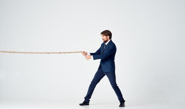 Geschäftsmann in einem anzug mit einem seil in seinen händen managerbüro heller hintergrund