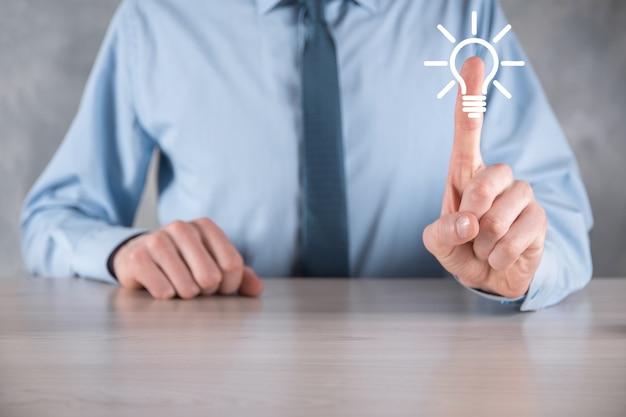 Geschäftsmann in einem anzug mit einer glühbirne in den händen. hält ein leuchtendes ideensymbol in der hand. mit platz für text