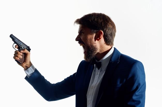 Geschäftsmann in einem anzug mit einer waffe in den händen detektiv vorsicht verbrechen