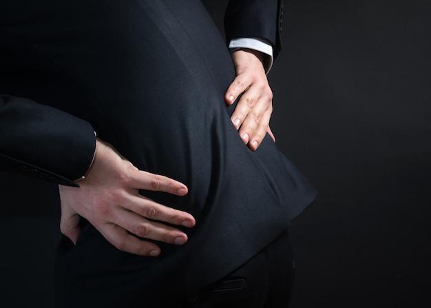 Geschäftsmann in einem anzug mit rückenschmerzen