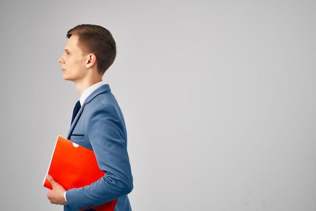 Geschäftsmann in einem anzug roter ordner in händen dokumente arbeiten professionell. foto in hoher qualität