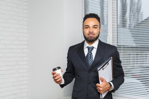 Geschäftsmann in einem anzug und in einem tasse kaffee