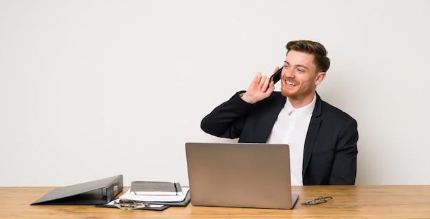 Geschäftsmann in einem büro, das ein gespräch mit dem handy hält