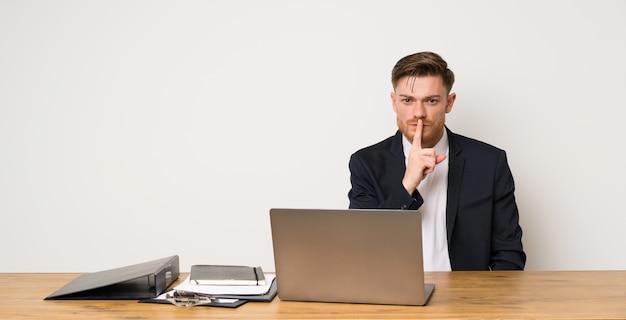 Geschäftsmann in einem büro, das ein zeichen der ruhegeste einsetzt finger in mund zeigt