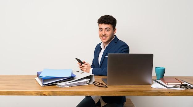 Geschäftsmann in einem büro, das eine mitteilung mit dem mobile sendet