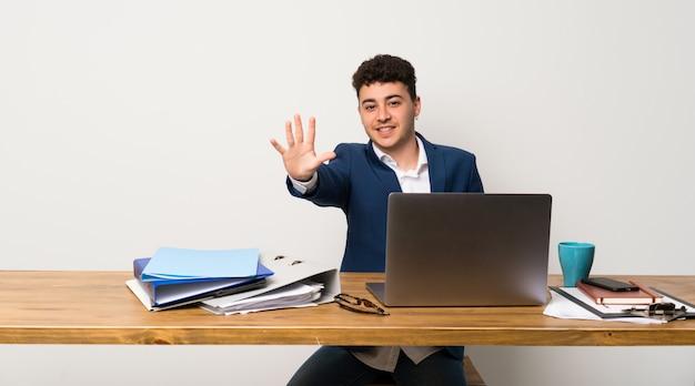 Geschäftsmann in einem büro, das fünf mit den fingern zählt