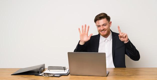 Geschäftsmann in einem büro, das sechs mit den fingern zählt