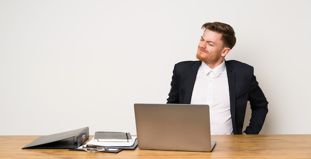 Geschäftsmann in einem büro, das unter rückenschmerzen leidet, weil er sich mühe gegeben hat