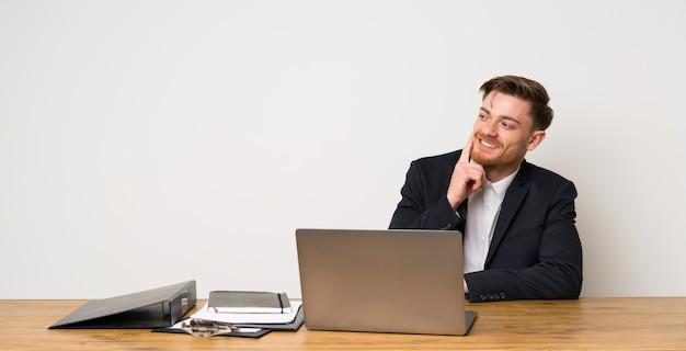 Geschäftsmann in einem büro eine idee beim oben schauen denkend