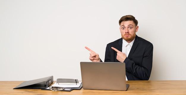 Geschäftsmann in einem büro erschrocken und auf die seite zeigend