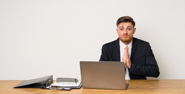 Geschäftsmann in einem büro hält palme zusammen. person bittet um etwas