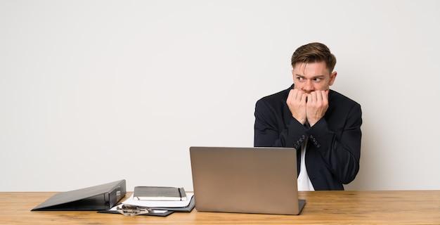 Geschäftsmann in einem büro nervös und erschrocken, hände zum mund setzend