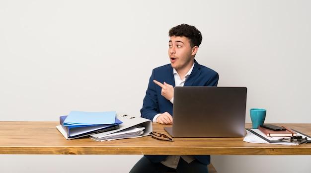 Geschäftsmann in einem büro überraschte und zeigende seite
