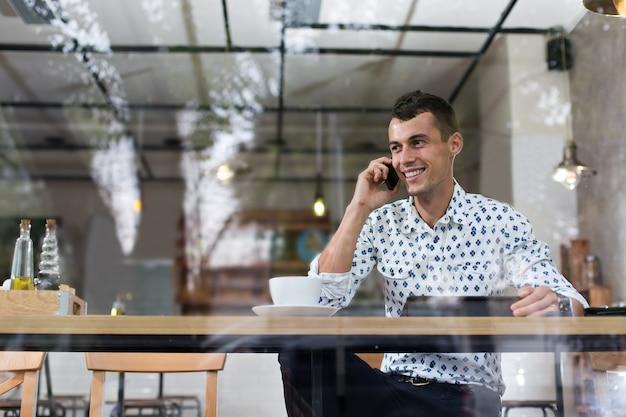 Geschäftsmann in einem café, das am telefon spricht
