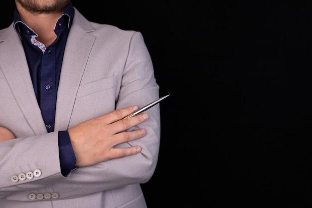 Geschäftsmann in einem grauen anzug mit verschränkten armen auf einem schwarzen hintergrund. geschäft, finanzen, ideen.