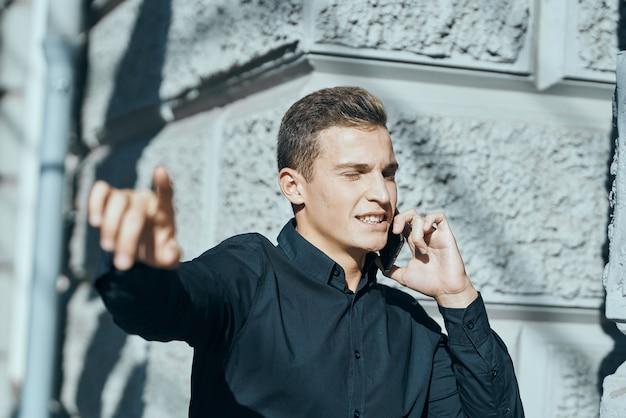 Geschäftsmann in einem hemd nahe dem gebäude mit dokumenten in seinen händen. hochwertiges foto