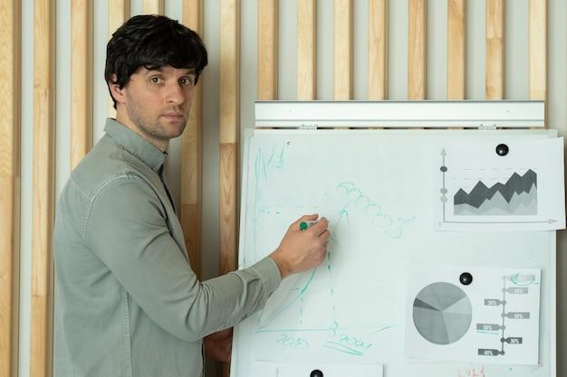 Geschäftsmann in einem hemd schreibt mit einem marker auf eine tafel, während er sich mit kollegen in einem büro unterhält, während die büromitarbeiter und manager ihm im büro aufmerksam zuhören