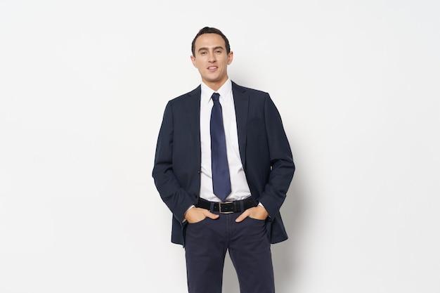 Geschäftsmann in einem klassischen anzug hält seine hände in den taschen. foto in hoher qualität