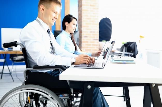 Geschäftsmann in einem rollstuhl, der an einem laptop arbeitet
