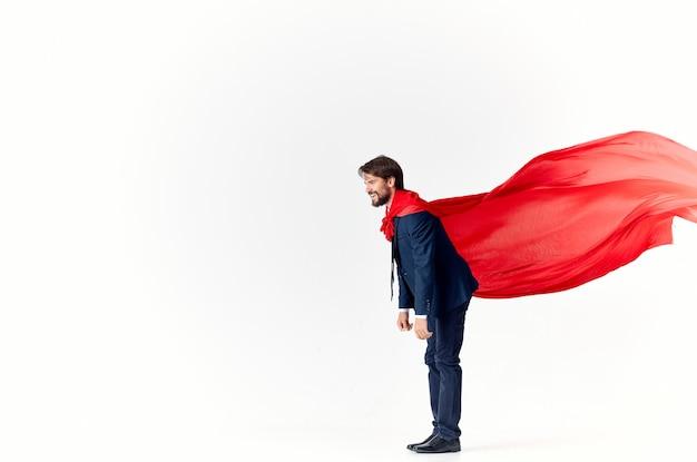 Geschäftsmann in einem roten umhang auf einem hellen raum gestikulierend mit seinen händen, die erfolg fliegen
