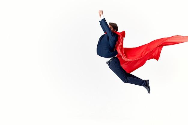 Geschäftsmann in einem roten umhang gestikuliert mit seinen händen, die erfolgswerbung fliegen