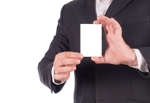 Geschäftsmann in einem schwarzen anzug, der eine karte über weiß hält