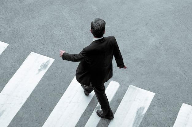 Geschäftsmann in einem schwarzen anzug überquert die straße an einem fußgängerüberweg, blick von oben