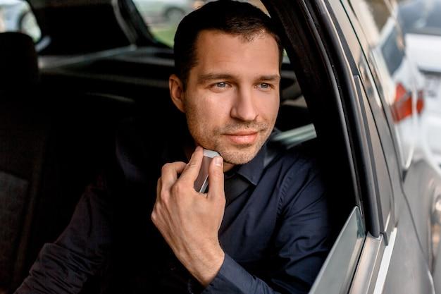 Geschäftsmann in einem taxi hält ein smartphone und schaut aus dem fenster. der passagier fährt auf dem rücksitz-nahaufnahmeporträt